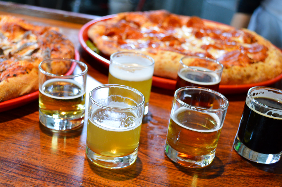 Pizza Port Brewing in Carlsbad, California. In a region known for outstanding craft beers, Pizza Port Brewing stands atop of the rest with craft beers that have racked up over 90 Great American Beer Festival medals. Belly up to the bar with me and let's enjoy a flight of Pizza Port Brewing beers!